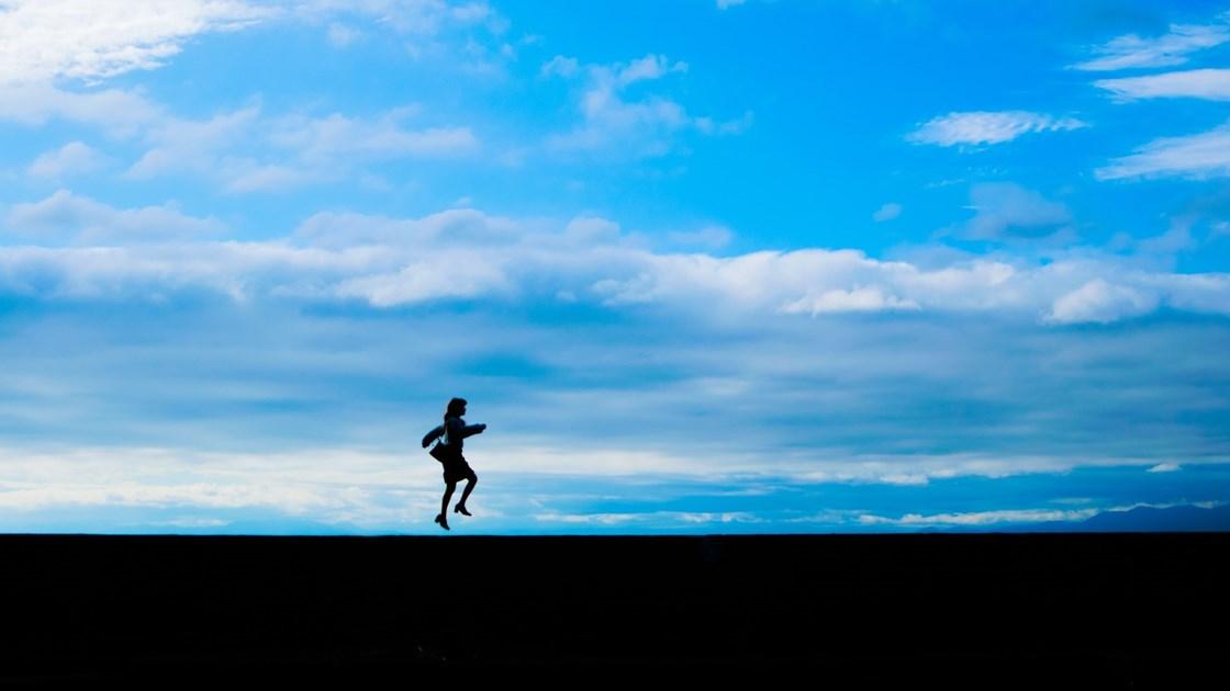 飛び上がる女性のシルエット